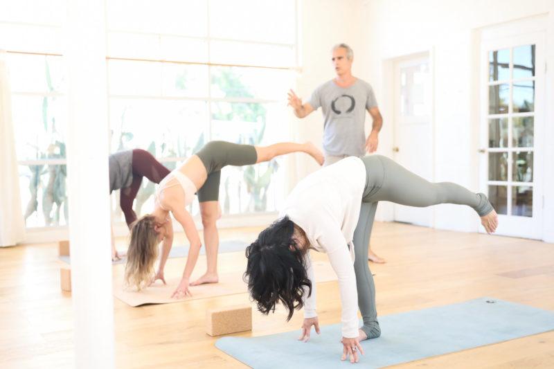 Bryan Kest teaching a yoga class with three students