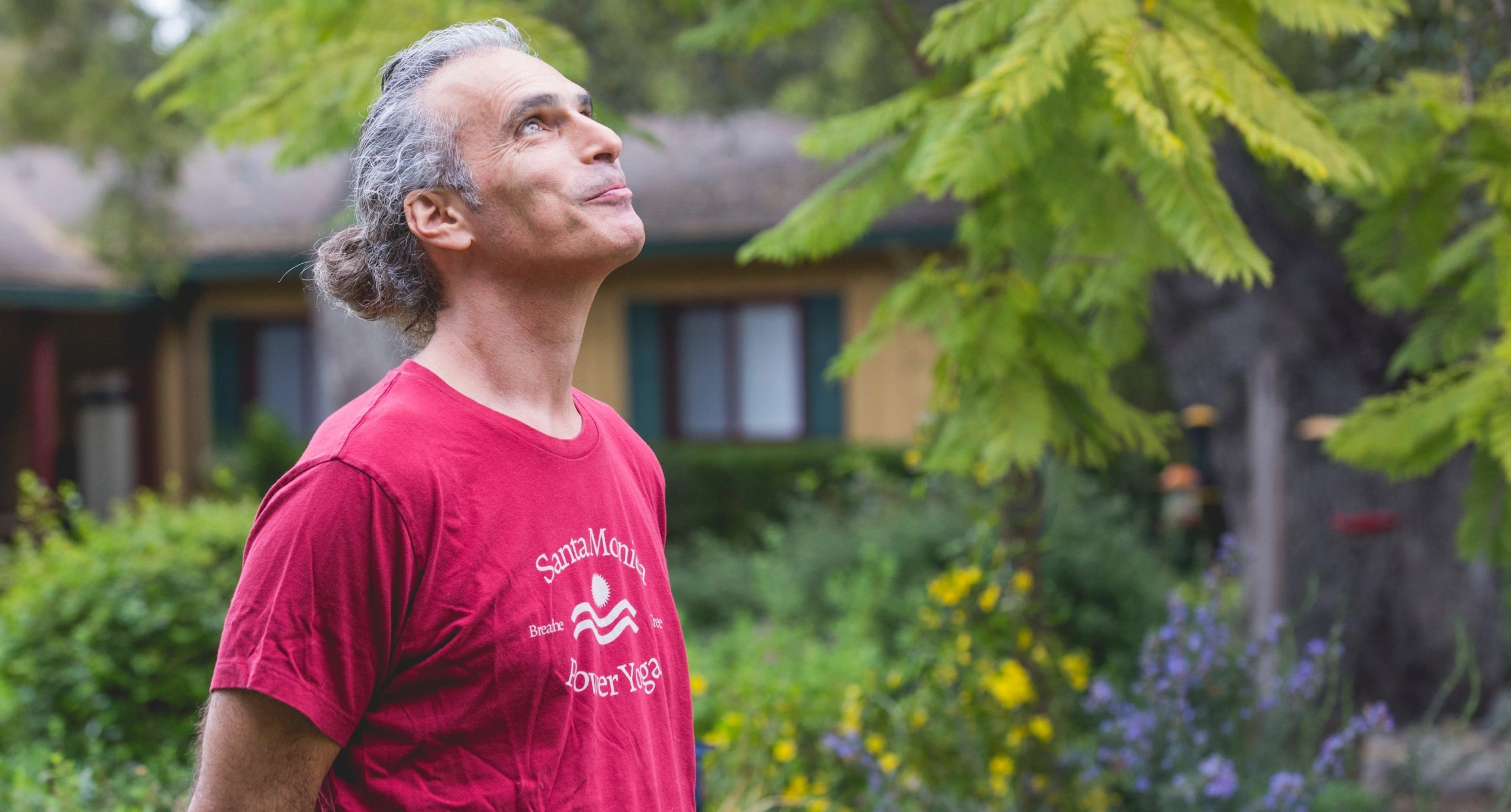 Bryan Kest wearing a red t-shirt in a garden looking up.