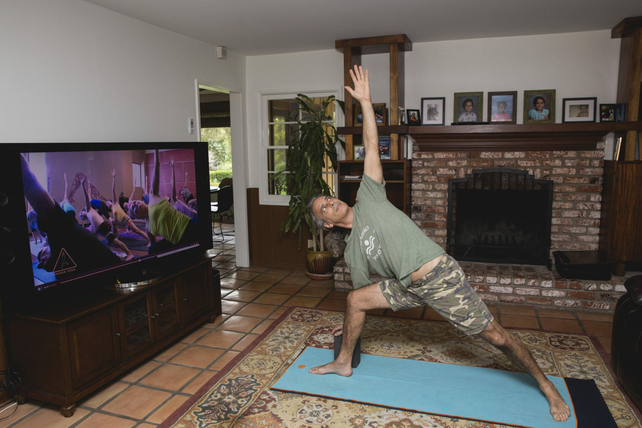 Bryan Kest doing a yoga pose in a living room.