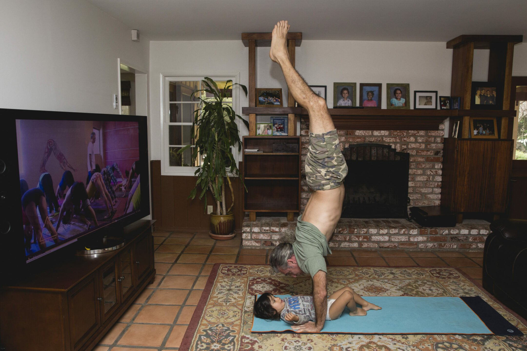 Bryan Kest doing handstand over a child