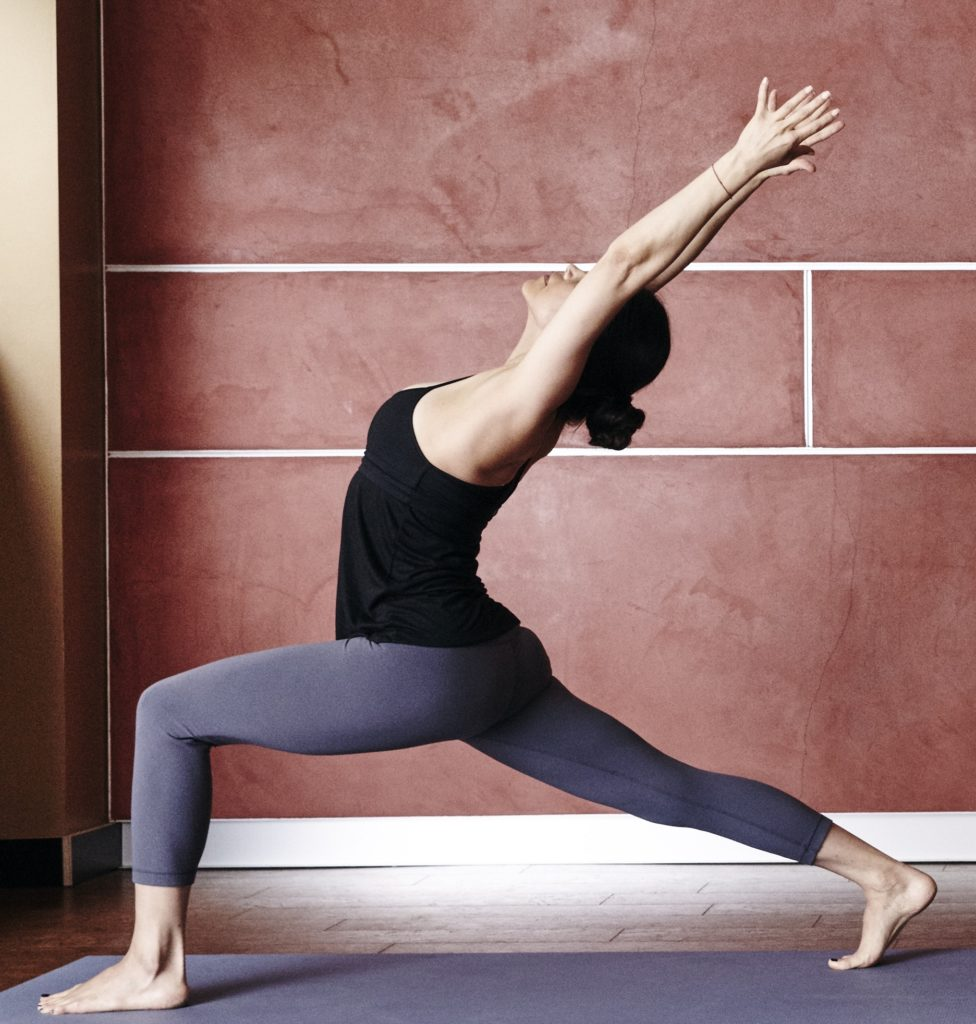 Woman doing crescent pose with back bend.
