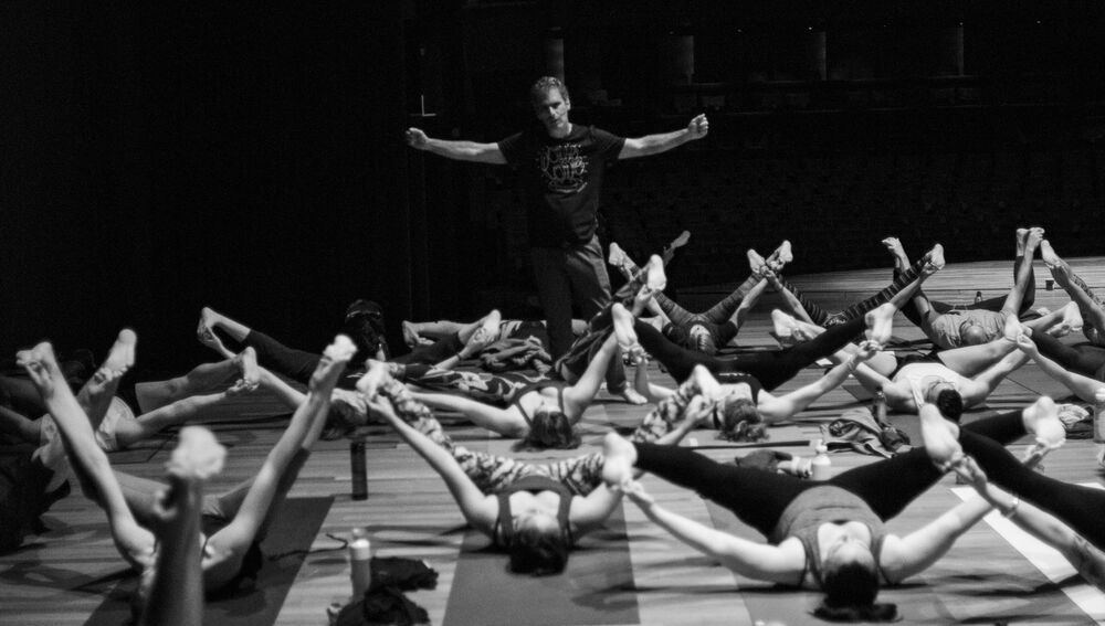 Black and white photo of brian kest leading a large yoga class